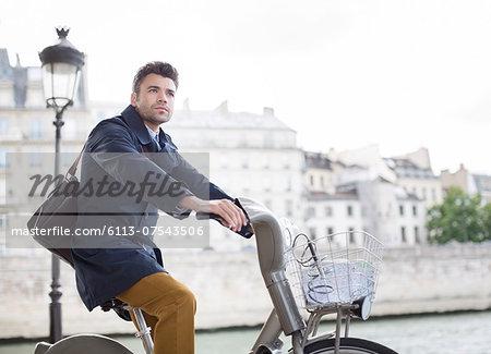 Businessman riding bicycle along Seine River, Paris, France