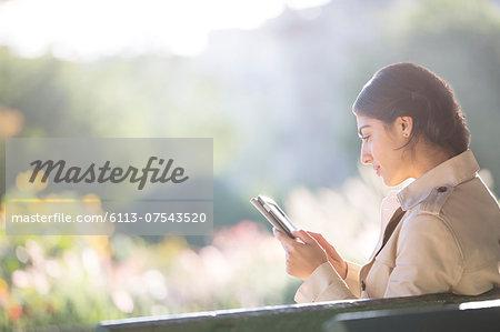 Businesswoman using digital tablet in park