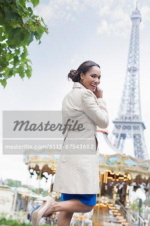 Woman walking near carousel and Eiffel Tower, Paris, France