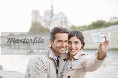 Couple taking self-portrait along Seine River near Notre Dame Cathedral, Paris, France