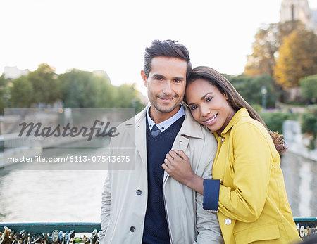 Couple hugging on Pont des Arts bridge over Seine River, Paris, France