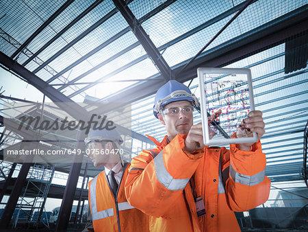 Builders working on plan details using digital tablet