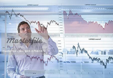 Businessman inspects graphs seen through interactive display