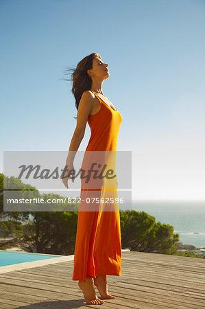 Woman Tiptoeing on Deck, Ocean in the background