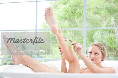 Woman in Bathtub Shaving Legs