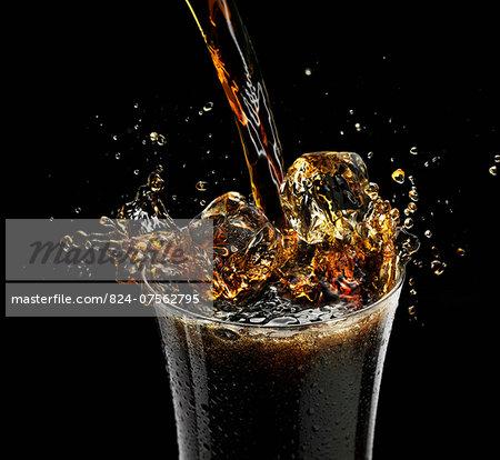Coca Cola splashing into a glass with ice