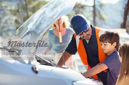 Boy watching roadside mechanic check car engine
