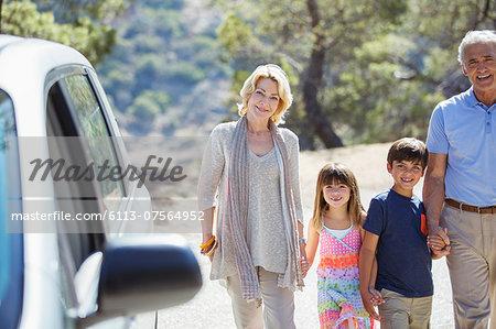 Grandparents and grandchildren holding hands outside car