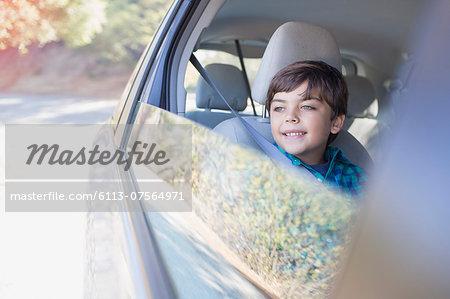 Happy boy looking out car window