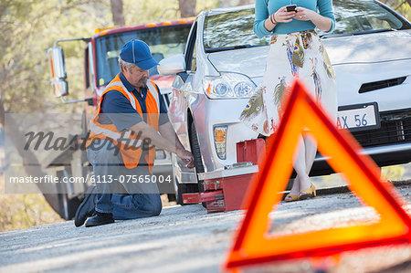 Roadside mechanic changing tire behind warning triangle