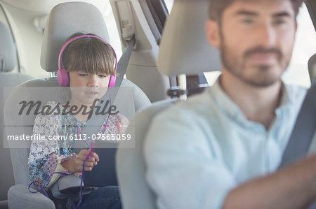 Girl with headphones using digital tablet inside car