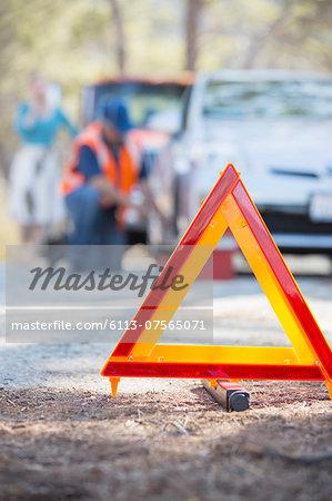 Roadside mechanic helping woman behind warning triangle