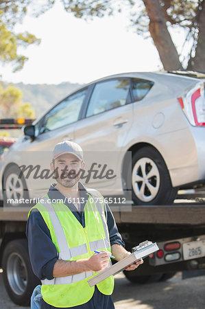 Portrait of confident roadside mechanic with paperwork