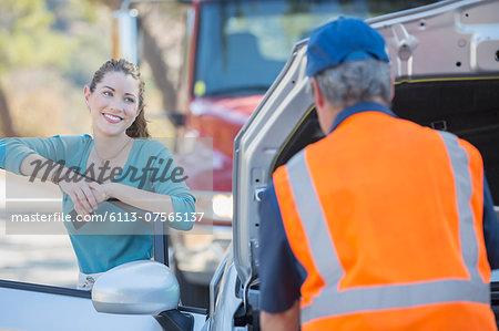 Grateful woman watching roadside mechanic fix car