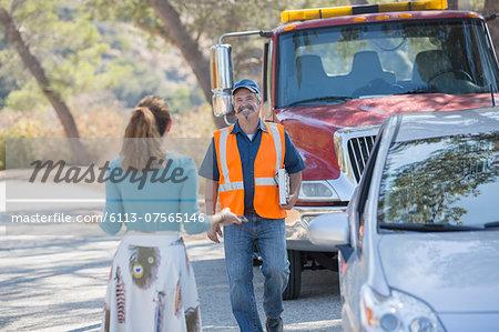 Woman greeting roadside mechanic
