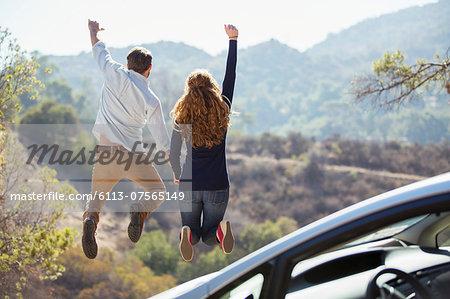 Enthusiastic couple jumping for joy outside car