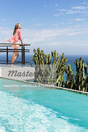 Woman basking in sun on poolside balcony overlooking ocean