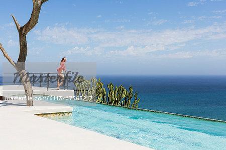 Woman standing on poolside balcony overlooking ocean