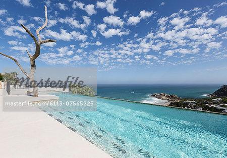 Clouds in blue sky over luxury lap pool overlooking ocean