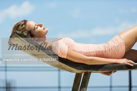 Woman in dress sunbathing on lounge chair