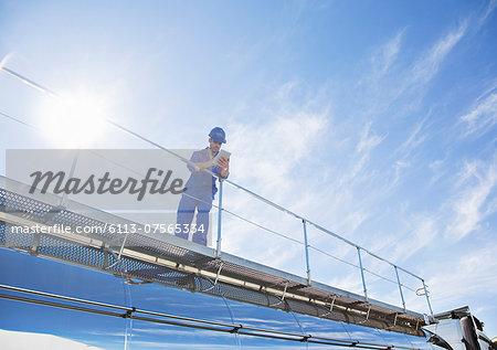 Worker with digital tablet standing on platform above stainless steel milk tanker