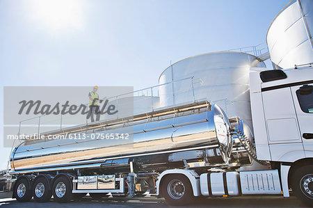 Worker on platform above stainless still milk tanker