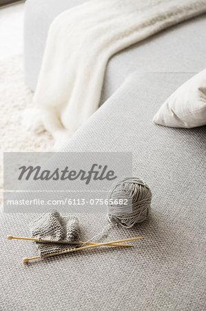 Knitting needles and ball of wool on sofa