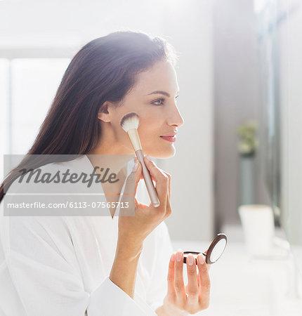 Woman in bathrobe applying makeup in bathroom