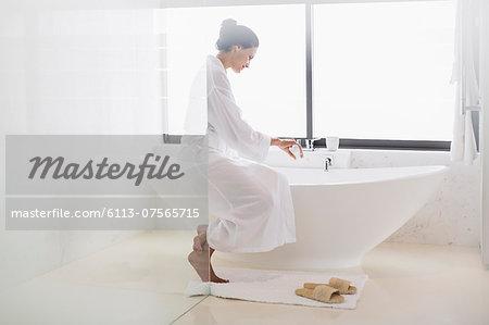 Woman in bathrobe preparing bath