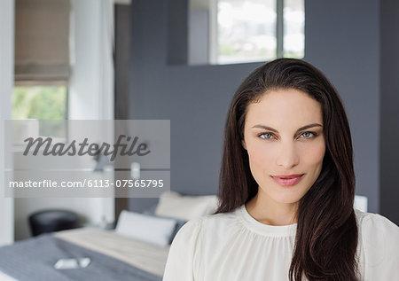 Portrait of confident woman in bedroom