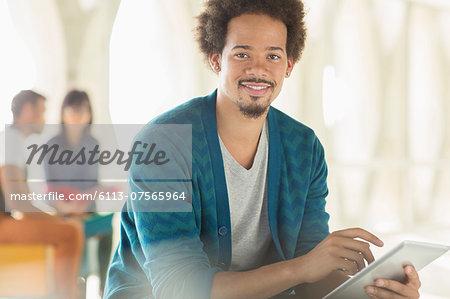 Portrait of casual businessman using digital tablet
