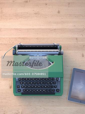Digital Illustration of Old Typewriter and Modern Tablet Computer on Wooden Desk