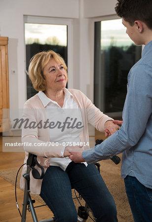 Teenage boy helping Grandmother sitting in walker at home, Germany