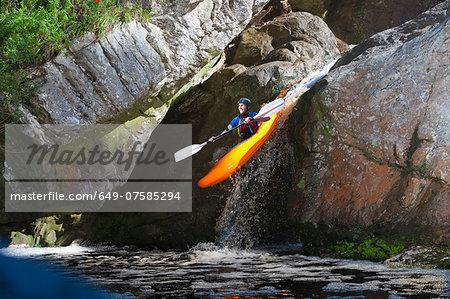 Mid adult man kayaking down river waterfall