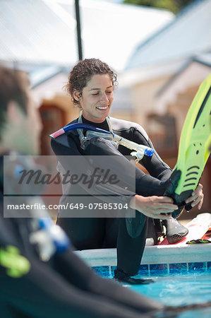 Young female scuba diver preparing to train in swimming pool