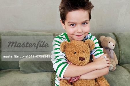Portrait of young boy on sofa hugging teddy