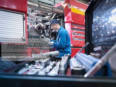 Engineer working on engine in truck repair factory