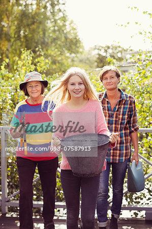 Portrait of three generation females with gardening equipment in yard