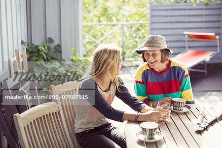 Grandmother and granddaughter having coffee in yard