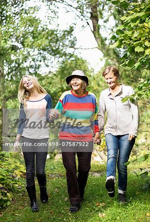 Happy three generation females walking in park