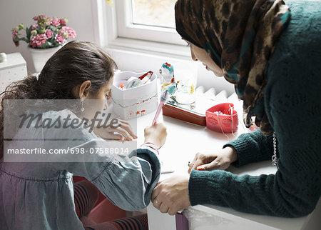 Mother helping girl in doing homework at desk