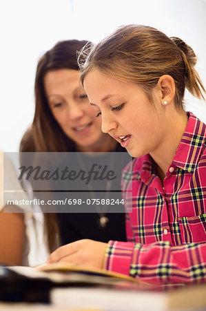 Teacher with schoolgirl studying in classroom