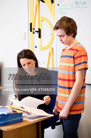 Teacher teaching high school boy at desk in classroom