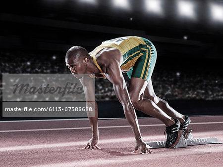 Runner poised at starting line on track