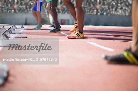 Runners standing at starting blocks on track