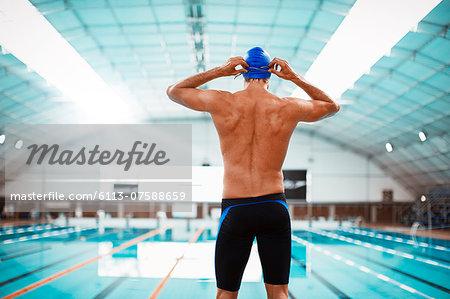 Swimmer adjusting goggles at poolside
