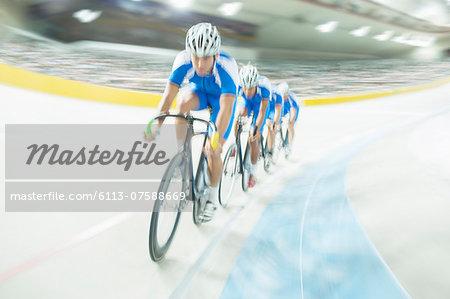 Track cycling team riding around velodrome