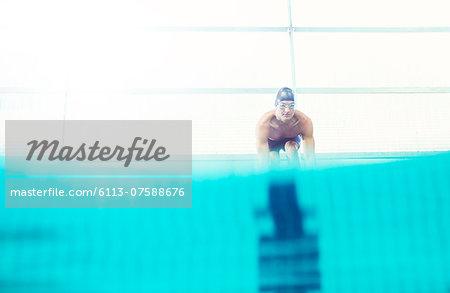 Swimmers poised on starting blocks