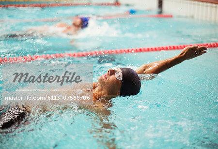 Swimmers racing in backstroke in pool