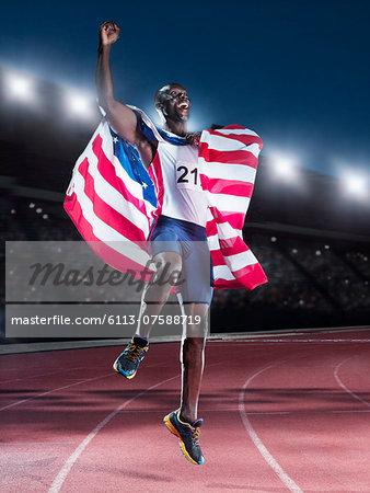 Runner holding American flag and celebrating on track